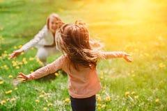 Kind die moeder` s handen tegenkomen om haar te koesteren Familie die pret in het park heeft Royalty-vrije Stock Foto