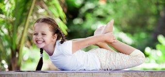 Kind die oefening op platform in openlucht doen Gezonde Levensstijl Het meisje van de yoga stock fotografie