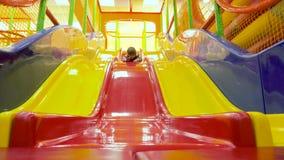 Kind die onderaan het kleurrijke huis van het diaspel in binnenplaats glijden Sporten en recreaties voor kinderen Spelen en spele stock videobeelden