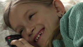 Kind die op Bed liggen die op TV, het Gelukkige het Glimlachen Portretmeisje Ontspannen op Bank letten stock footage
