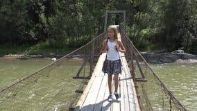 Kind die op Brug in Bergen, Jong geitje in Aard, Meisje wandelen die een Rivier, Stroom kijken stock videobeelden