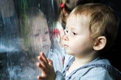 Kind die op de regen op venster letten