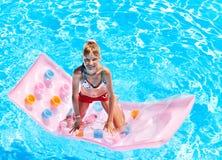 Kind die op strandmatras zwemmen. Stock Foto