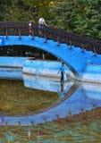 Kind die op water onder een brug lopen Stock Foto