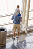Kind die op zijn vadersschouders uit een heldere luchthavenwind kijken Stock Fotografie
