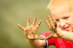 Kind die openlucht tonende vuile modderige handen spelen stock foto's