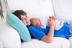 Kind die pasgeboren sibling houden Stock Afbeelding
