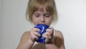 Kind die pret hebben die slijm maken Jong geitje het spelen met hand - gemaakt stuk speelgoed slijm stock video