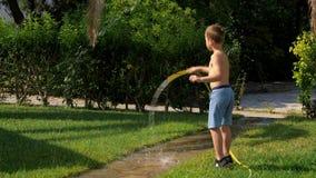 Kind die pret hebben wanneer het water geven van gazon met slang stock footage
