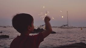 Kind die pret met een fonkelende gloed hebben bij zonsondergang stock footage
