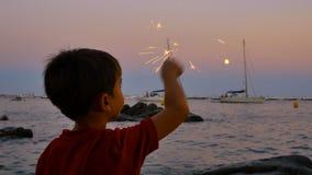 Kind die pret met een fonkelende gloed hebben bij zonsondergang stock video