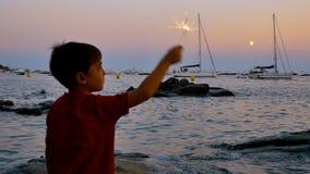 Kind die pret met een fonkelende gloed hebben bij zonsondergang stock videobeelden