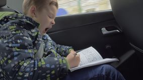 Kind die schaakraadsels in de auto oplossen stock videobeelden