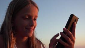 Kind die Smartphone, Jong geitje op Strand bij Zonsondergang spelen, Meisje die Tablet op Kust gebruiken stock video