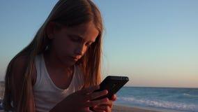 Kind die Smartphone, Jong geitje op Strand bij Zonsondergang spelen, Meisje die Tablet op Kust gebruiken stock footage