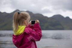 Kind die smartphonecamera met behulp van Stock Foto