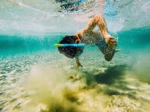 Kind die snorkeler de bodem bereiken stock fotografie
