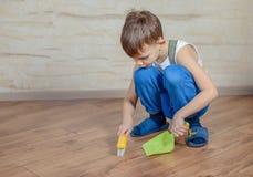 Kind die stuk speelgoed bezem en blik gebruiken stock afbeeldingen
