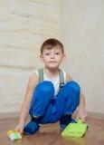 Kind die stuk speelgoed bezem en blik gebruiken stock foto's