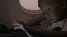 Kind die tabletpc in vliegtuig met behulp van stock footage