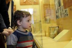 Kind die tentoongesteld voorwerp bekijken Stock Foto's