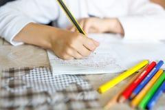 Kind die thuiswerk doen en verhaalpoging schrijven Elementaire of lage schoolklasse Close-up van handen en kleurrijke potloden stock foto