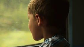 Kind die uit het venster van het bewegen van trein kijken stock videobeelden