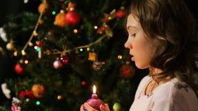 Kind die uit verfraaide Kerstmiskaars blazen en een wens, magische ogenblikken maken stock footage