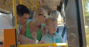 Kind die vaders gebruiken smartwatch tijdens busrit stock videobeelden