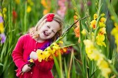 Kind die verse gladiolenbloemen plukken Stock Foto