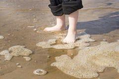 Kind die zich op het zand in ondiep water bevinden Royalty-vrije Stock Fotografie