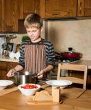 Kind dienende Borsjt, traditionele Russische en Oekraïense soep Gietende soep in een plaat met gietlepel van pan in keuken Royalty-vrije Stock Afbeeldingen