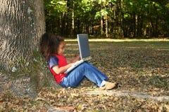 Kind draußen mit Laptop Lizenzfreie Stockbilder