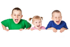 Kind drei hinter weißem Vorstand lizenzfreies stockbild