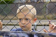 Kind durch Zaun lizenzfreies stockbild