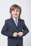 Kind in einem klassischen Anzug richtet seine Jacke gerade Stockfoto