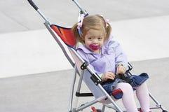Kind in einem Spaziergänger Stockfotos