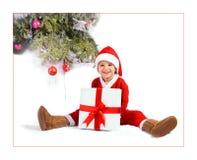 Kind in einem Weihnachtsmann-Kostüm mit einem Geschenk. Lizenzfreies Stockbild
