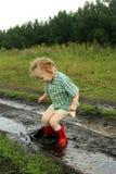 Kind in einer Pfütze Stockbilder