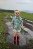 Kind in einer Pfütze Stockfotos