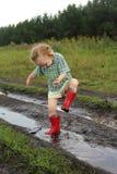 Kind in einer Pfütze Lizenzfreies Stockfoto