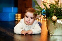 Kind in einer weißen Strickjackenlüge nahe bei dem Kasten mit Tannenzweigen auf dem Hintergrund von Weihnachtslichtern und -gesch Lizenzfreie Stockfotos