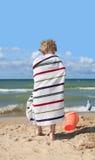 Kind eingewickelt in einem Tuch am Strand Lizenzfreie Stockfotos