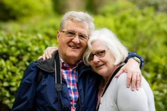 A kind elderly couple, cuddling and smiling at the camera stock images