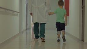 Kind en arts die in het ziekenhuisgang lopen stock videobeelden
