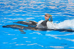 Kind en dolfijnen die in blauw water zwemmen. Stock Foto