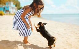 Kind en hond het spelen op het strand stock foto's