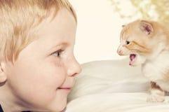 Kind en katje die elkaar onder ogen zien Stock Afbeeldingen