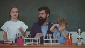 Kind en leraar in de klassenruimte met bord op achtergrond Jong geitje van lage school Mijn chemieexperiment stock videobeelden
