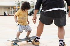 Kind en leraar die leren te schaatsen stock foto's